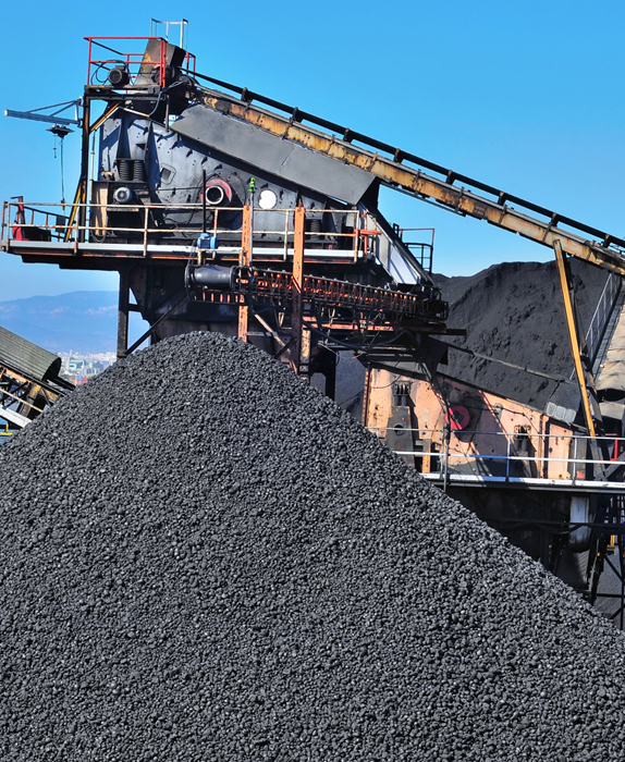 Large pile of coal and machinery in background
