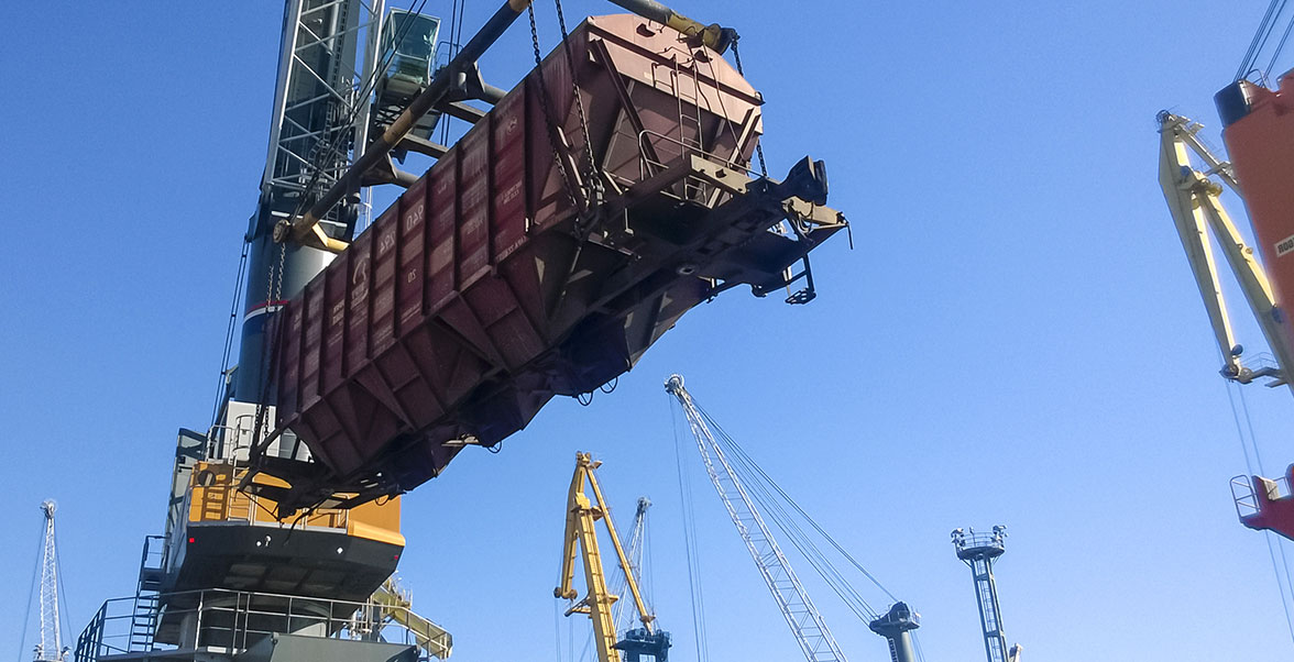 crane lifting project cargo—a train coal car—at a port