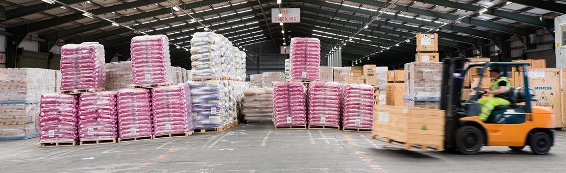inside-port-warehouse-forklift-driving-past-pallets-of-cargo