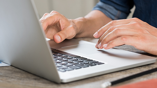 closeup of man's hands typing on laptop